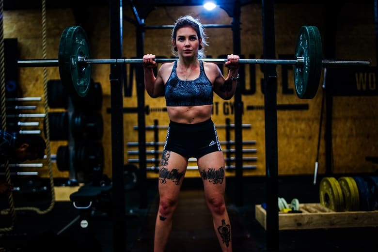 woman squatting in front of power rack back squats explanation definition lmao 2plate