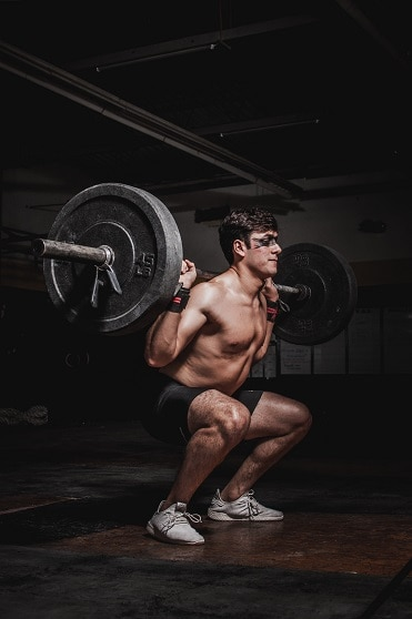 squatting at the gym lifting heavy weights for massive muscle gains and hypertrophy